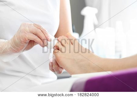Pedicure, beautiful healthy nails. Woman in a beautician at a pedicure. Pedicure in the beauty salon. Foot and nail care treatment, woman at beautician on pedicure.