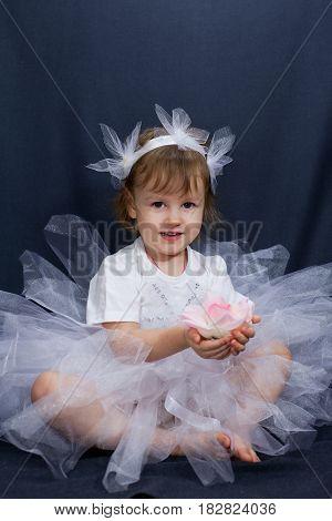 Little ballerina posing on a black background