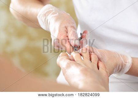 Pedicure. Pedicure, cutting skins. Pedicure, nail clipping. Nail clipping at the feet, woman on pedicure. The beautician cuts the skin with fingernails and performs professional pedicure.