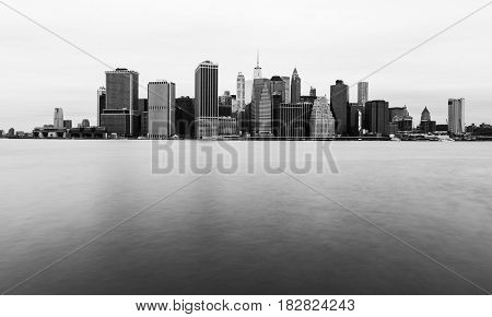 Manhattan skyline in cloudy day, New York skyscrapers reflected in water, black and white photo, USA