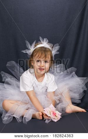Ballerina  in a white dress on a black background