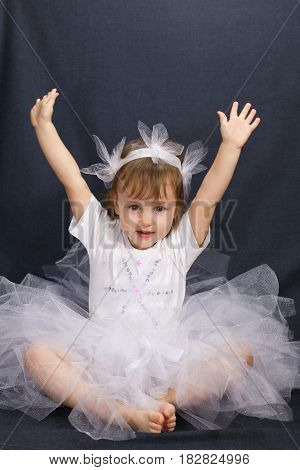Ballerina is dancing in a white dress on a black background