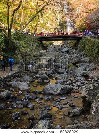 Minoo waterfall with red bridge in autumn at Minoo or Minoh national park in Osaka, Japan . One of Japan's oldest national parks.