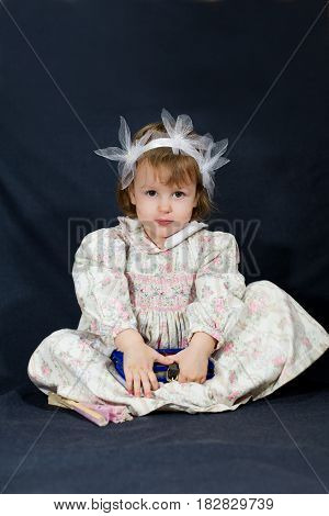 Cute little girl holding a book. Black background