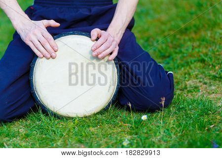 Drummer man with her djembe drum on meadow