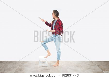 Beautiful young woman in working clothes holding paintbrushes, trying paint on wall, ready for home renovation.