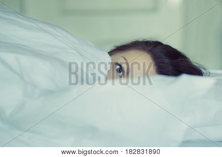 A beautiful female lies in bed and can not fall asleep and reads news on the smartphone. Insomnia. Psychology. Phobias