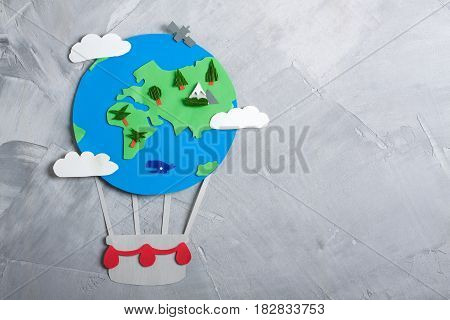 Paper craft earth globe handmade on gray concrete background. Earth day concept. Horizontal orientation top view.