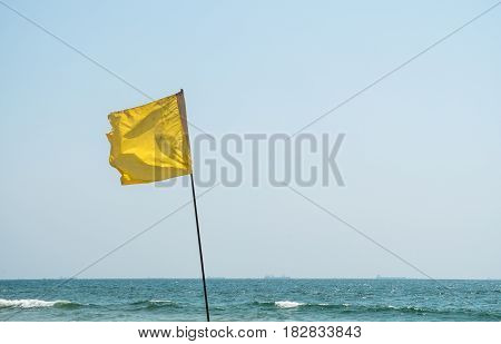 Yellow warning flag in Goa, India, with blue sky as background