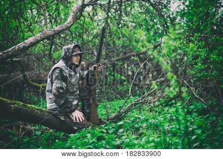 A man hunter with a gun sits on a fallen tree in rainy weather in a spring forest toned photo