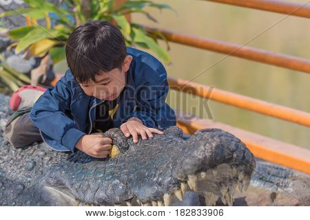 image of young cute asian boy play with crocodile doll.
