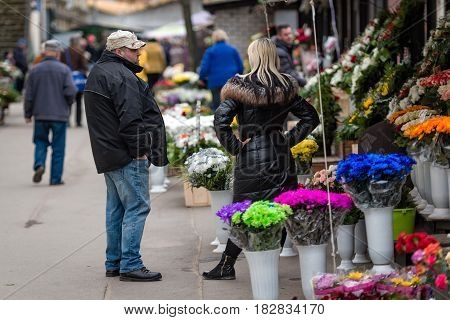 RIGA LATVIA - APRIL 13 2016: Unknown flower merchant talking to a man at a flower shop.