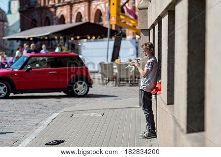 RIGA LATVIA - MAY 4 2016: Unknown boy on the street playing the flute.