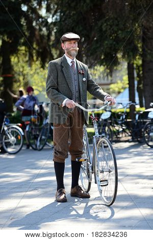 RIGA LATVIA - MAY 7 2016: Tweed ride. Unknown male in historical garments with an ancient bicycle.