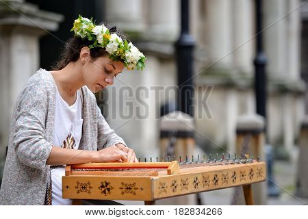 RIGA LATVIA - JULY 27 2016: Unknown girl in traditional costume on the street plays a harp.