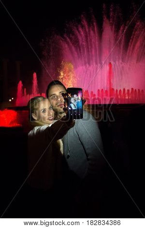BARCELONA SPAIN- NOVEMBER 28 2014: Two unknown young people in the evening at the musical fountains photographing selfie.
