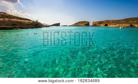 Comino Malta - The beautiful azure sea water at the Blue Lagoon on the island of Comino on a bright sunny summer day