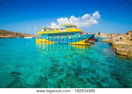 BLUE LAGOON COMINO MALTA - OCTOBER 17 2016: Visitors and tourists arriving on a boat to enjoy the clear turquoise water and the other wonders of the Blue Lagoon on the island of Comino Malta.