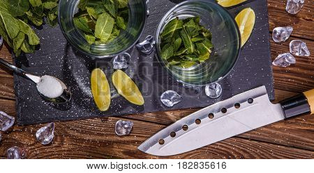 Mojito cocktail with mint, ice, lime, on stone black board