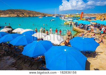 BLUE LAGOON COMINO MALTA - October 18 2016: Tourists crowd to enjoy the clear turquoise water under umbrellas on a sunny day in October 18 2016 in Comino island Malta with the island of Gozo at background.