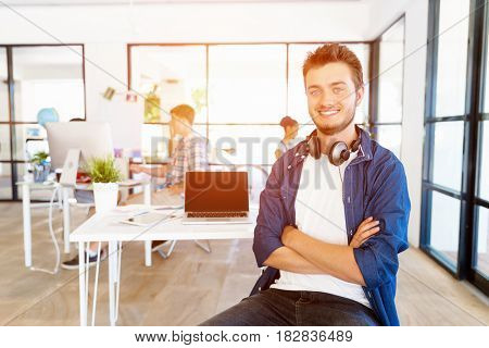 Young man sitting and looking at camera in office