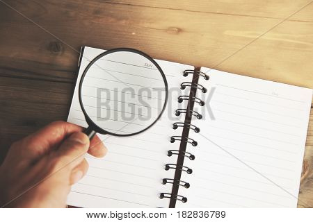 notebook with a magnifying glass on a wooden background