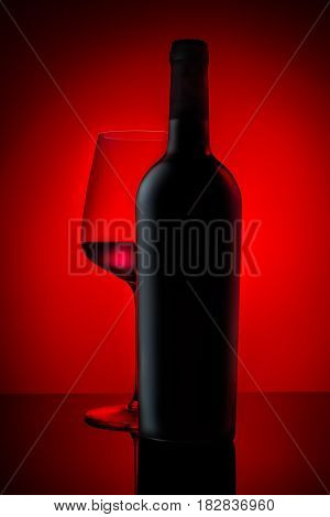Red wine bottle with wineglass on red background