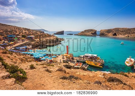 Comino Malta - Tourists crowd at Blue Lagoon to enjoy the clear turquoise water on a sunny summer day with clear blue sky and boats on Comino island Malta.