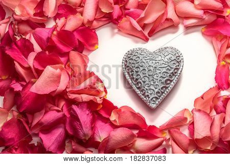 Decorative carved heart in heart frame shape of red rose petals on white background