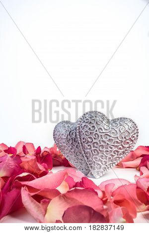 Couple of decorative carved hearts in red rose petals on isolated white background