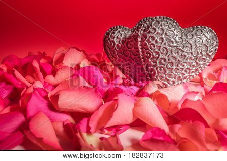 Couple of decorative carved hearts in red rose petals on red  background