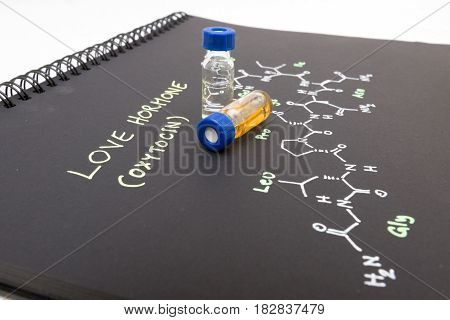 Close-up Blue Cap Sample Vial On Notebook With Chemical Formula Of Oxytocin (love Hormone)