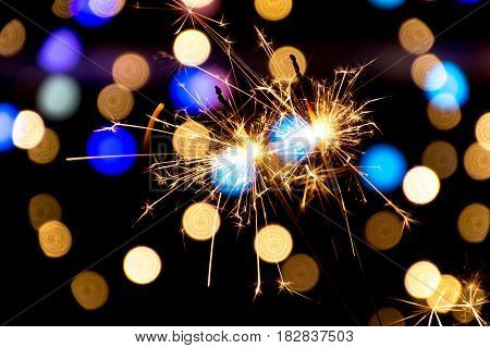 Two burning sparklers at black background with many colorful lights