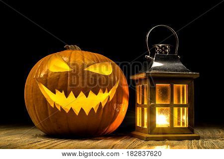 Halloween pumpkin with lantern and candle light at old wooden table with black background