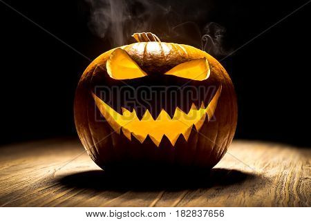 Smiling pumpkin with smoke at wooden rustic table