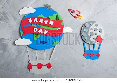 Paper craft earth globe moon flag rocket handmade on gray concrete background. Earth day concept lettering. Horizontal orientation top view.
