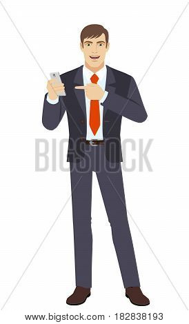 Businessman pointing at a mobile phone. Full length portrait of businessman in a flat style. Vector illustration.