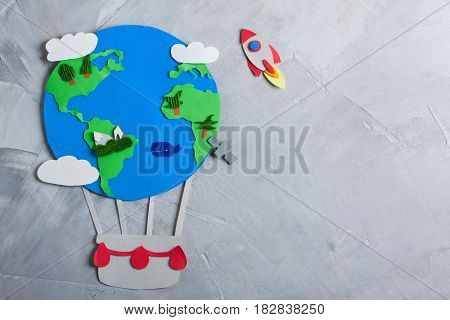 Paper craft earth globe rocket handmade on gray concrete background. Earth day concept. Horizontal orientation top view.