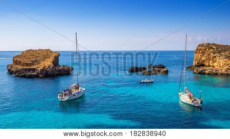 Comino Malta - Sailing boats at the beautiful Blue Lagoon at Comino Island with turquoise clear sea water blue sky and rocks in the water
