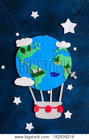 Paper craft earth globe rocket white stars handmade on blue wooden background. Earth day concept. Vertical orientation top view.