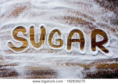Word of sugar written on wooden background