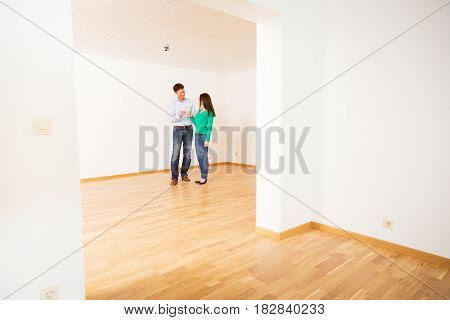 adult couple celebrating their new apartment with a glass of champagne