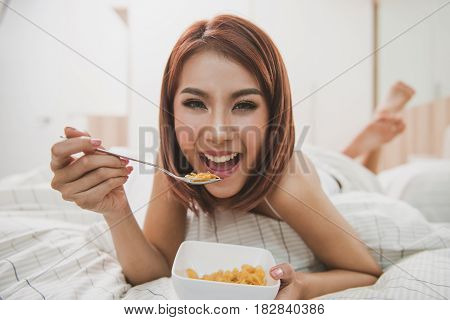 Happy woman enjoying cornflakes cereals in the bed in the morning.