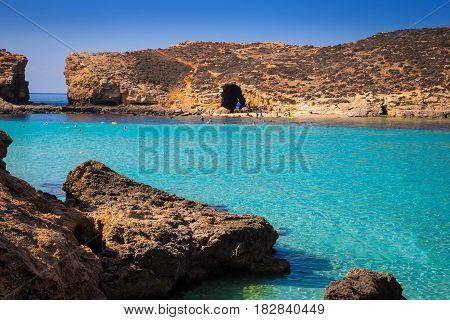 Comino Malta - Beautiful azure sea water at the famous Bluw Lagoon of Comino with snorkeling tourists enjoying the summer sunshine