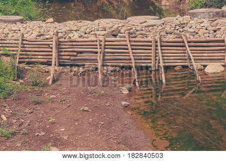 vintage tone image of man made weir(small dam) made from bamboo and rock across the river on day time.