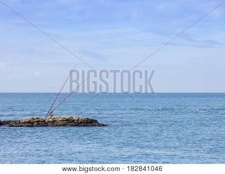Sea fishing rods on a rocky outcrop