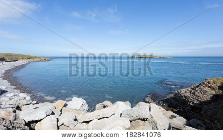 Rocky coastline at Moelfre Anglesey in North Wales with distant view of Moelfre Island (Ynys Moelfre)