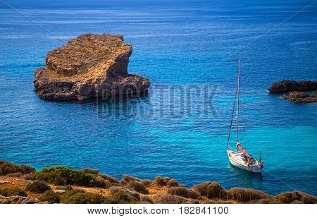 Blue Lagoon Malta - Sailing boat at the famous Blue Lagoon at the Island of Comino on bright sunny summer day with crystal clear azure sea water