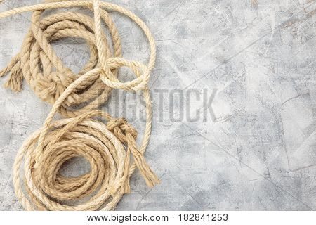 White rope with knot on gray background. Top view. Place for text.