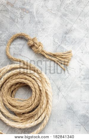 Ship rope knot on light gray concrete background. Top view. Place for text.